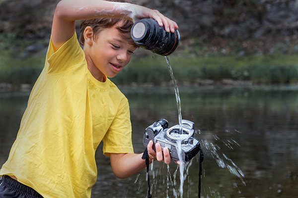 a child pouring water onto a camera